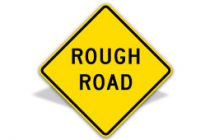 Custom yellow diamond sign reading rough road