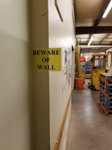 A yellow and black caution: beware of wall sign.