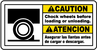 Caution Chock wheels before loading or unloading - Atencion Asegurar las llantas antes de cargar o descargar bilingual sign